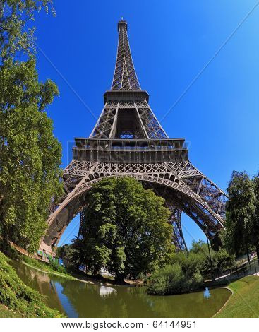 Huge and beautiful Eiffel Tower. At the foot of the tower is designed park with paths and pond. The picture was taken Fisheye lens