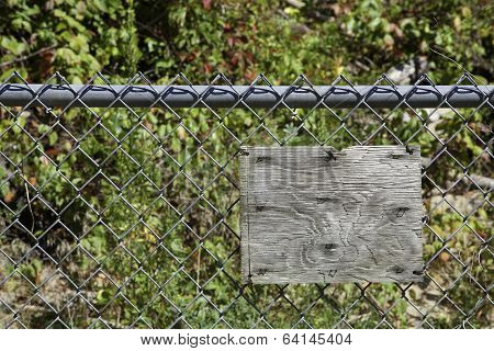 Blank Rustic Wooden Sign On Chain Link Fence