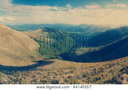 Sunny day in the mountains. Summer landscape with a mountain valley. Carpathians, Ukraine, Europe. Filtered image: vintage, grunge and texture effects