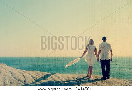 Loving couple looking at the sea holding hands. Filtered image: vintage, grunge and texture effects