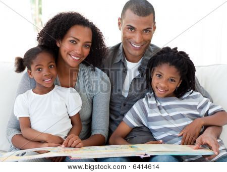 Portrait Of An Afro-american Family Reading A Book In The Living-room