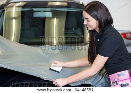 Car Wrappers Using Squeegee To Straighten Vinyl Film