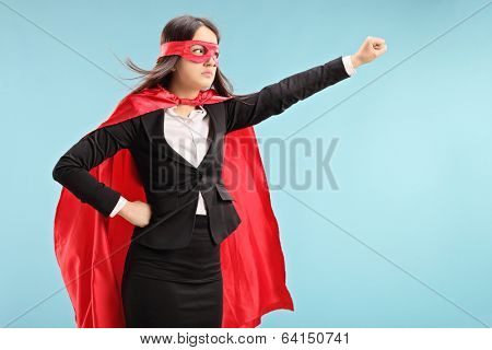 Female superhero with raised fist on blue background