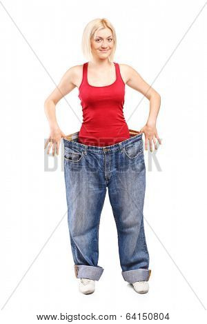 Woman standing in a pair of oversized jeans isolated on white background