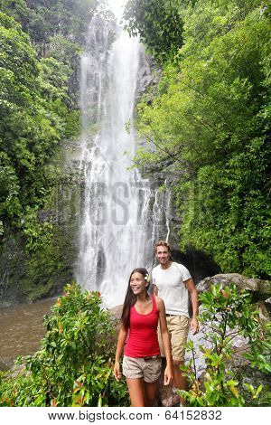 Hawaii tourist hiking people. Couple happy by waterfall during travel on the road to Hana on Maui, Hawaii. Ecotourism concept image with happy backpackers. Interracial Asian / Caucasian young couple.