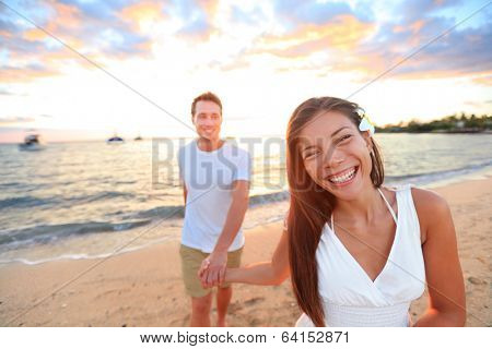 Happy couple on beach holding hands at sunset in romantic walk at night during honeymoon summer vacation travel holidays. Multi-ethnic couple, young Asian woman and Caucasian man.