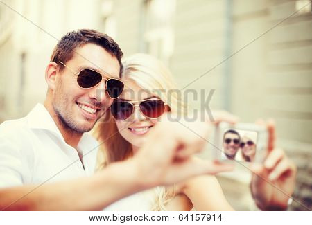summer holidays and dating concept - couple taking photo in cafe in the city