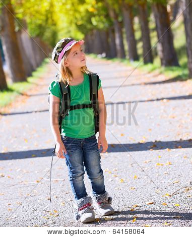 Blond explorer kid girl walking with backpack in autumn trees track