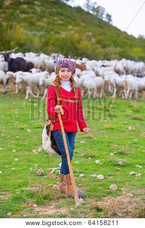 Kid girl shepherdess happy with flock of sheep and wooden stick in Spain
