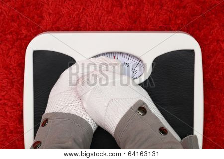 Female feet on bathroom scale