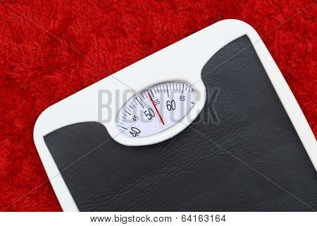 Bathroom scale on red bath mat