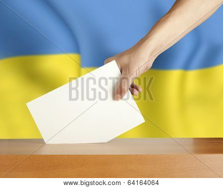 Female hand with ballot and box on Flag of Ukraine