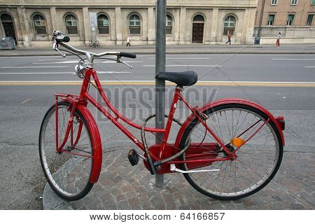 BOLOGNA, ITALY - APRIL 19, 2014: A bicycle stands locked to a pole on a street in Bologna, Italy, on Saturday, April 19, 2014.