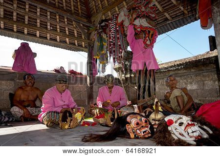 BALI - APRIL 13, 2014: Balinese actors prepare with costume change and make-up before commencing a 'Barong' performance in a temple in Bali, Indonesia. The  Barong depicts benevolence overcoming evil.