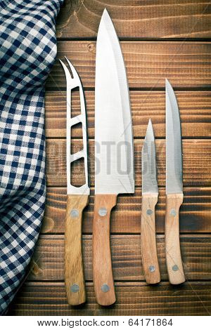 set of kitchen knives on old wooden table
