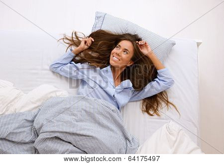 Young Woman Awake In Bed And Smiling