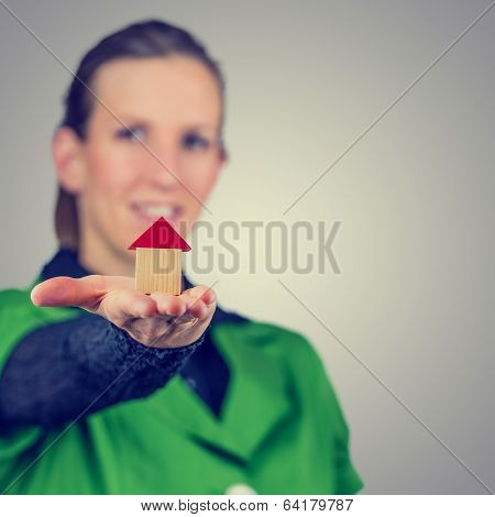 Female Real Estate Agent Holding Out A Model House