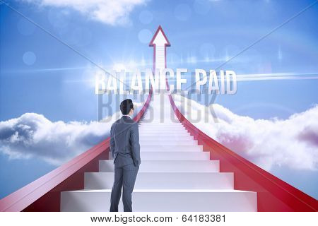 The word balance paid and businessman standing against red steps arrow pointing up against sky