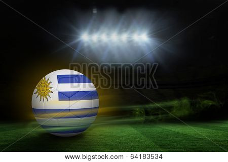 Football in uruguay colours against football pitch under spotlights