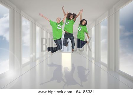 Enviromental activists jumping and smiling against bright white hall with windows