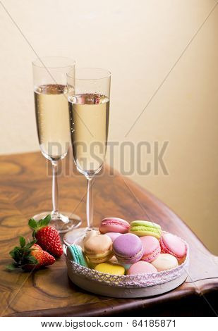Two glasses of sparkling wine or champagne with small colorful macaroons
