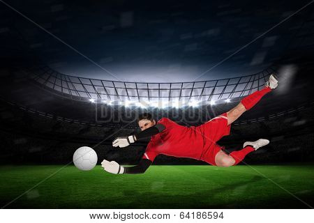 Fit goal keeper jumping up against large football stadium with fans in yellow