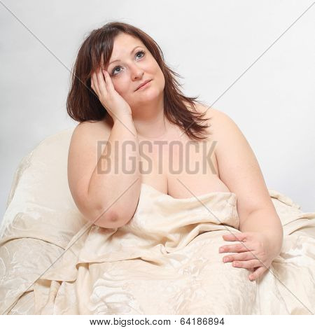 Overweight woman wake up. Early morning in the bedroom.