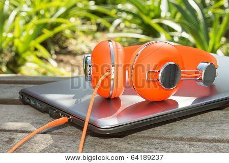 Bright Coloured Orange Headphones And Mobile Computer