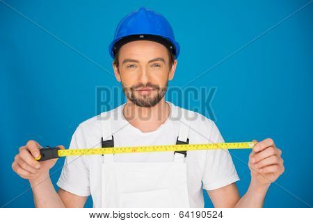 Smiling young workman wearing a hardhat and dungarees standing holding a tape measure extended in his hands against a blue background