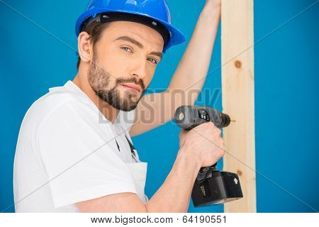 Carpenter or builder wearing a hardhat standing in front of a blue wall drilling a hole in a plank of wood with a handheld battery-operated drill