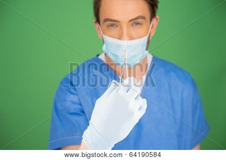 Male nurse or doctor wearing surgical scrubs and a mask holding up a pair of forceps in front of his face on a green background