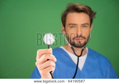 Handsome young male anaesthetist or doctor holding a stethoscope up with the disk facing the camera and the ear pieces in his ears as though he is listening, on a blue background