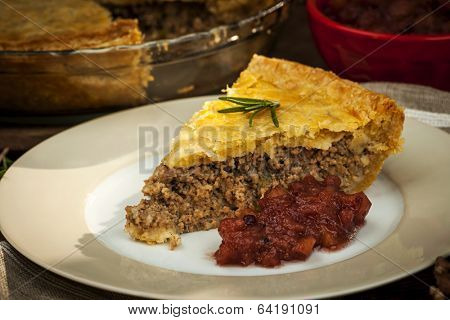Slice of traditional pork meat pie Tourtiere with apple and cranberry chutney from Quebec, Canada.