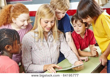 Teacher giving class with tablet computer in elementary school