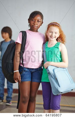 Two female friends together on schoolyard in elementary school