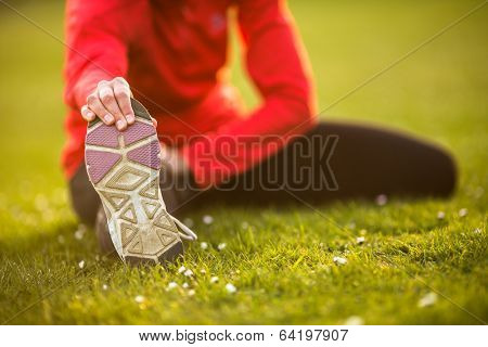 Young woman stretching before her evening run