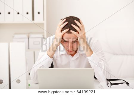 man sitting in office resting his forehead in hands