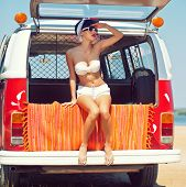 stock photo of recreational vehicle  - a beautiful young girl in retro look with red lips in a white swimsuit a bandana and sunglasses is sitting in the car trunk and is looking in the distance - JPG