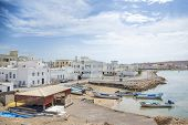 stock photo of oman  - Image of a view to Sur harbor in Oman with sea mountains boats houses and sky - JPG