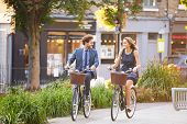 stock photo of commutator  - Businesswoman And Businessman Riding Bike Through City Park - JPG