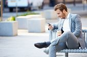 stock photo of bench  - Businessman On Park Bench With Coffee Using Mobile Phone - JPG
