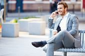 foto of bench  - Businessman On Park Bench With Coffee Using Mobile Phone - JPG