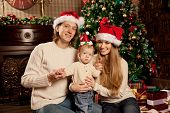 pic of christmas baby  - Happy smiling young family near the Christmas tree celebrate New Year - JPG