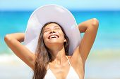 foto of sun-tanned  - Beach woman enjoying sun tanning on travel smiling under blue sky - JPG