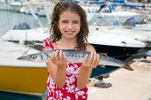 picture of barracuda  - Happy kid fisherwoman with barracuda fish catch in Mediterranean marina - JPG