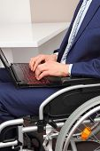 stock photo of physically handicapped  - a Businessman in a Wheelchair with laptop - JPG