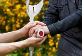 stock photo of crutch  - Close up of an elderly hand holding a crutch - JPG