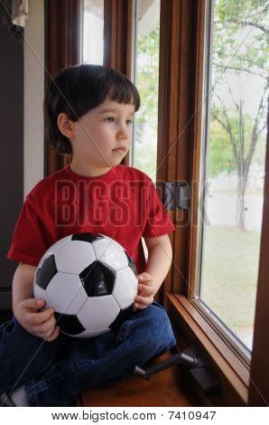 Boy will spielen Fußball an einem regnerischen Tag