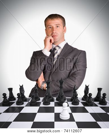 Lost in thought businessman and chess board