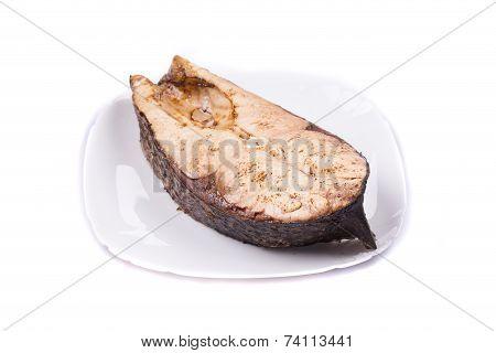 Fish steak on the round plate.